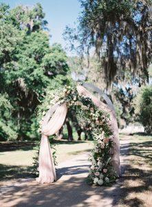 Allestimento cerimonia diurno con arco di tessuti e fiori
