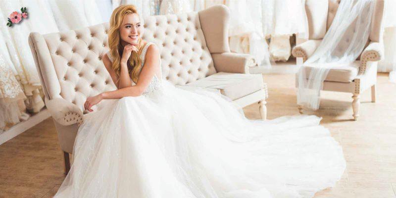 Sposa in abito bianco seduta in atelier