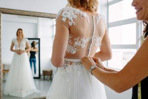 Sposa che prova l'abito con schiena effetto tattoo nude