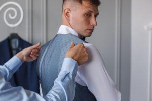 Sposo misura l'abito indossando il gilet sopra la camicia bianca