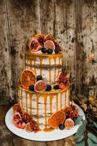 Torta nuziale al caramello e cacao ispirata all'autunno con arance, melagrane, uva e fichi