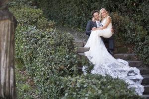 Sposo che tiene in braccio la sposa con un abito in pizzo dal lungo strascico