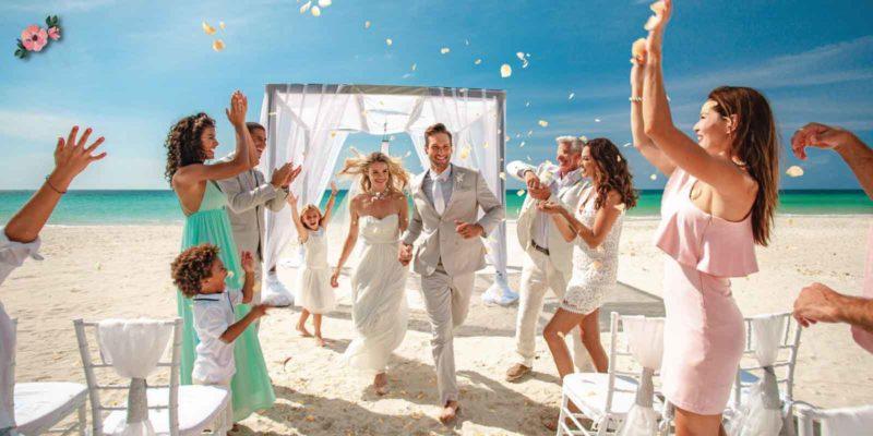 Sposi e amici festosi in spiaggia dopo il rito del matrimonio