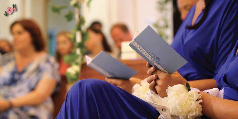 Damigelle in blu seguono la cerimonia sul libretto messa