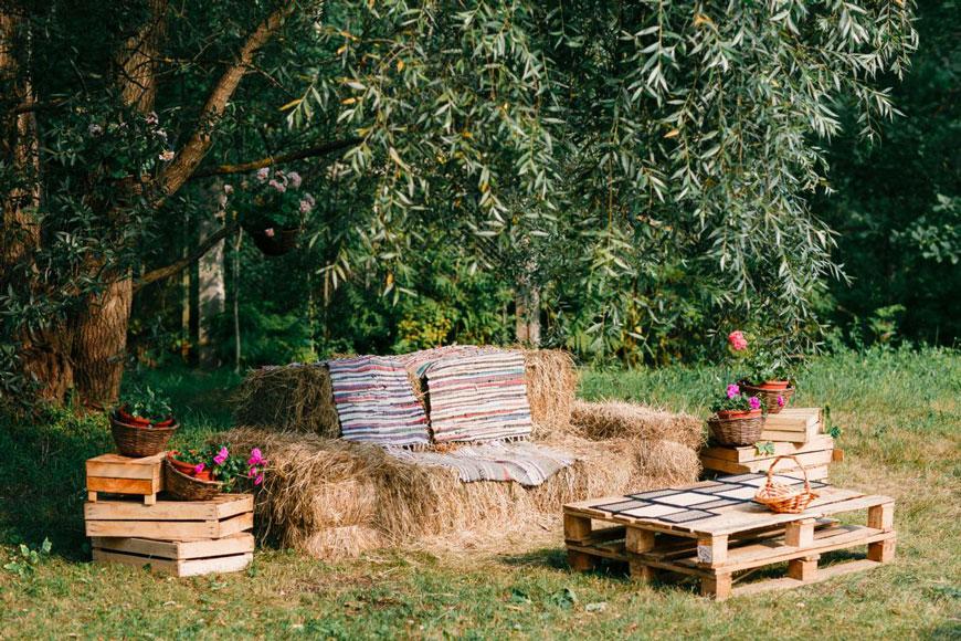 Zona relax allestita in stile country con balle di paglia e cassette di legno