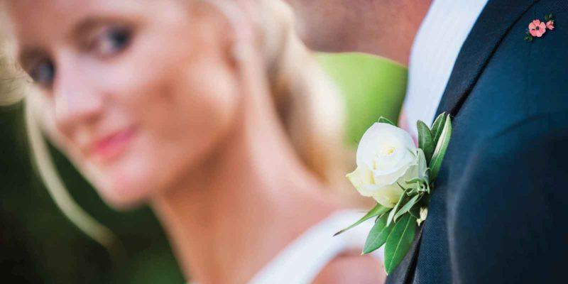 Boutonnière dello sposo in primo piano sotto il dolce sguardo della sposa