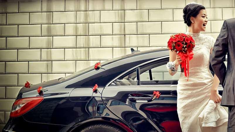Auto degli sposi decorata con fiorellini rossi sparsi