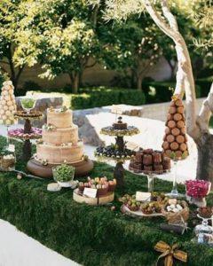 Tavolo del buffet di dolci ricoperto con il prato per il tema Alice nel Paese delle Meraviglie